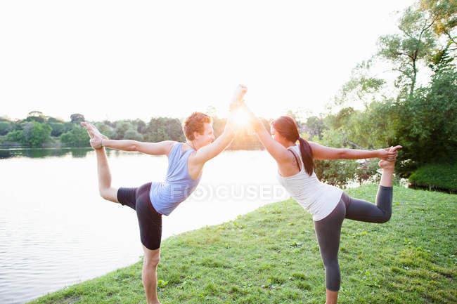 Paar praktiziert Yoga am Wasser — Stockfoto