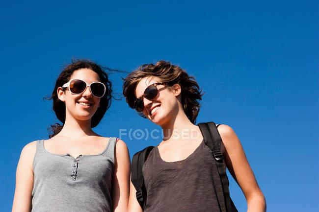 Mulheres sorrindo juntas contra o céu claro — Fotografia de Stock