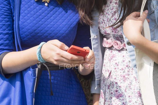 Дві жінки, за допомогою смартфона, середині розділі — стокове фото