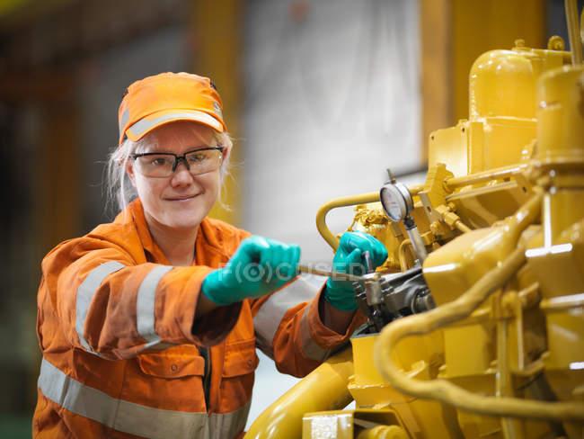 Female apprentice engineer with engine — Stock Photo