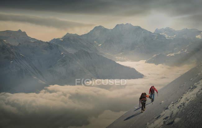 Due arrampicatori su un pendio innevato sopra un mare di nebbia in una valle alpina, Alpi, Canton Wallis, Svizzera — Foto stock