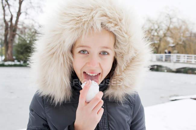 Дівчина в хутряній витяжці облизує сніг — стокове фото