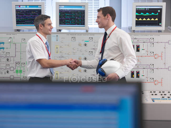 Operators shaking hands in control room — Stock Photo