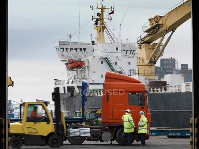Портовиків з Лоррі і корабель — стокове фото
