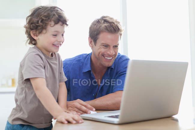 Vater und Sohn nutzen gemeinsam Laptop — Stockfoto