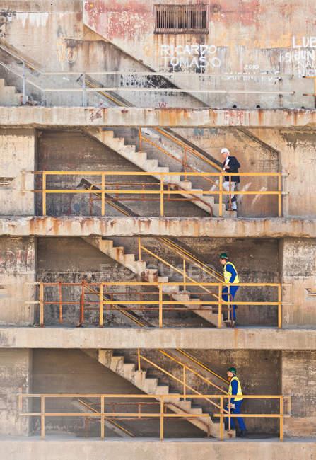Рабочие поднимаются по ступенькам в сухом доке — стоковое фото