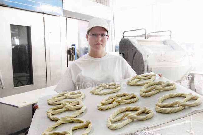Baker holding baking sheet of pretzels — Stock Photo
