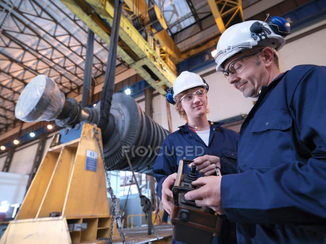 Ingénieurs avec turbine et grue — Photo de stock