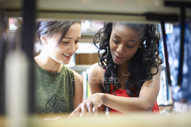 Two young female college students pointing at book on library shelves — Stock Photo