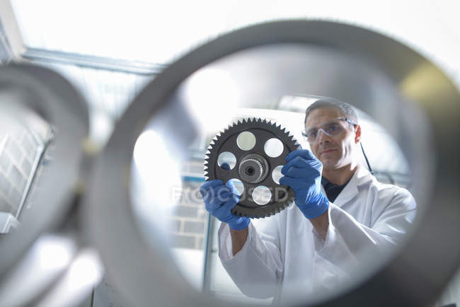 Worker inspecting engineering products that are being cleaned using ultrasonics, view through equipment — Stock Photo