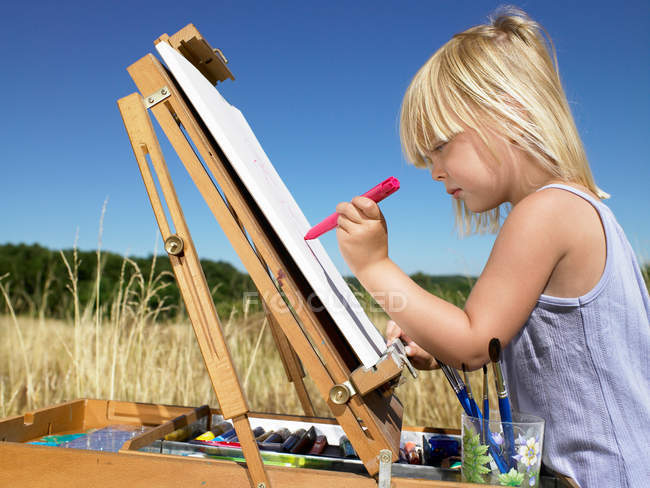 Ritratto della ragazza che dipinge in un campo — Foto stock