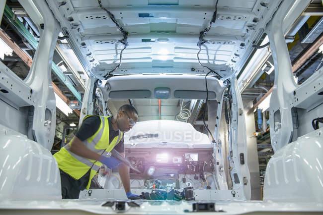 Operaio automobilistico che indossa parti di montaggio giacca ad alta visibilità sul veicolo sulla linea di produzione in fabbrica di auto — Foto stock