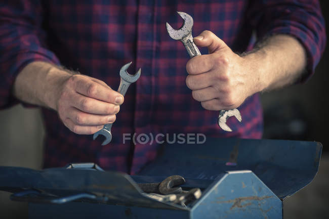 Man holding different sized spanners — Stock Photo