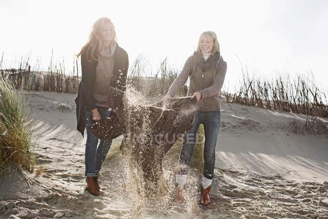 Donne scuotendo fuori spiaggia coperta — Foto stock