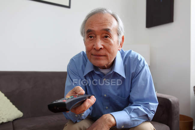 Older man watching television — Stock Photo