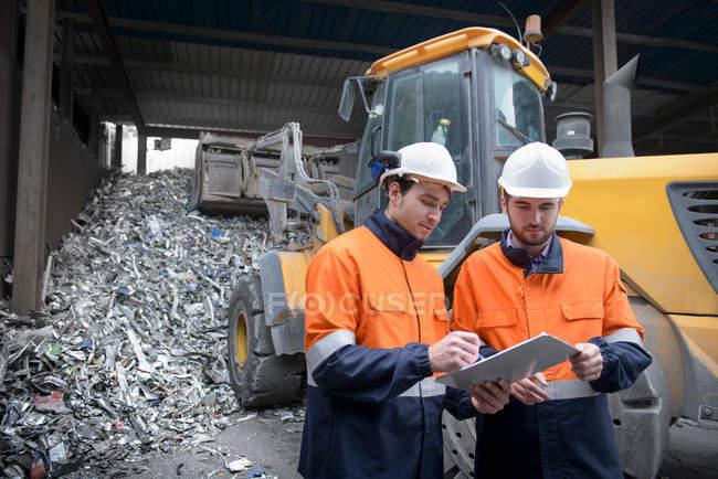 Працівників, переглядаючи документи в переробки пластмасових перед металобрухт алюмінієвий — стокове фото