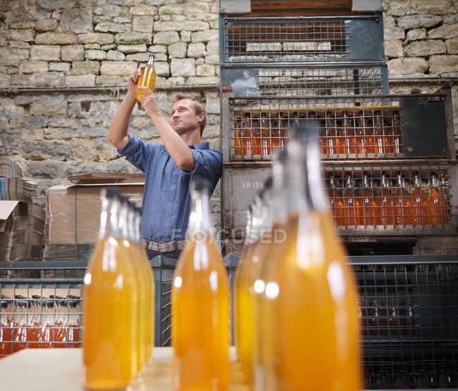 Человек с бутылкой органического сидра — стоковое фото