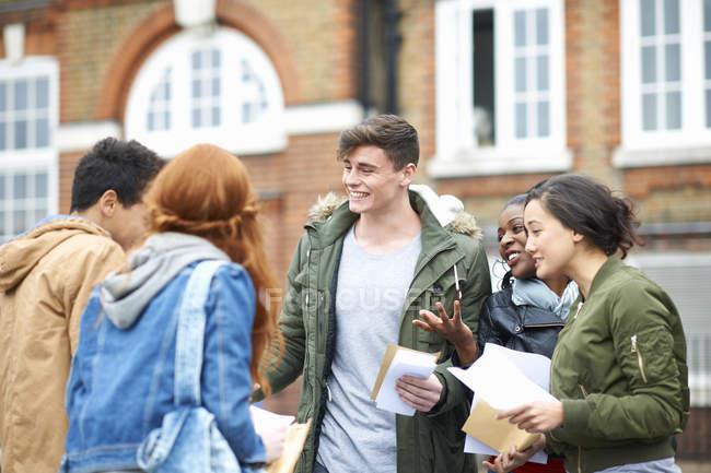 Studenti di college adulto giovane felice congratulandosi con ogni altri risultati di esami nel campus — Foto stock