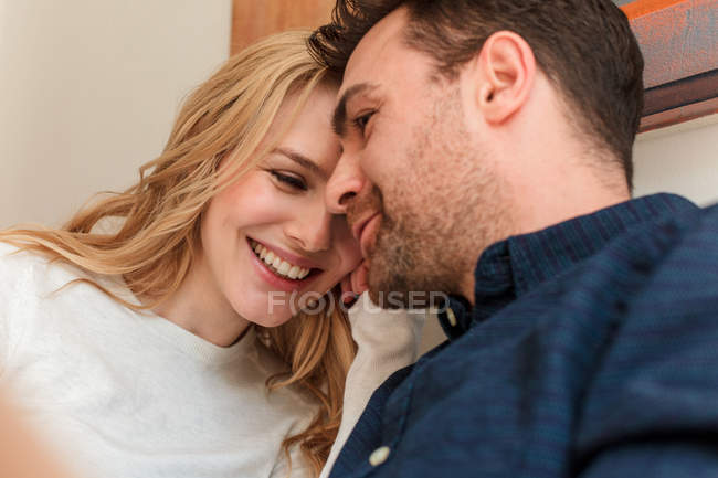 Couple snuggling together and smiling at home — Stock Photo