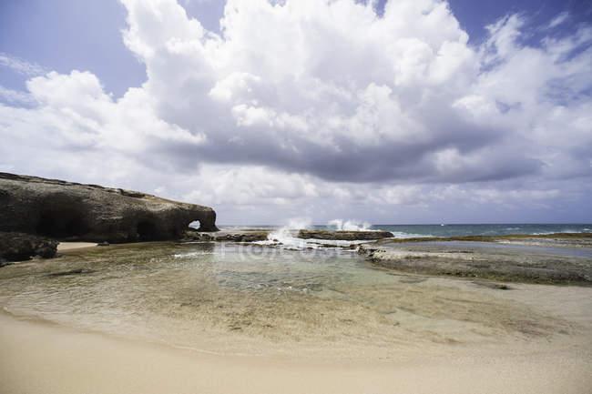 Vue du dessous de la plage de sable vide sous un ciel nuageux bleu — Photo de stock