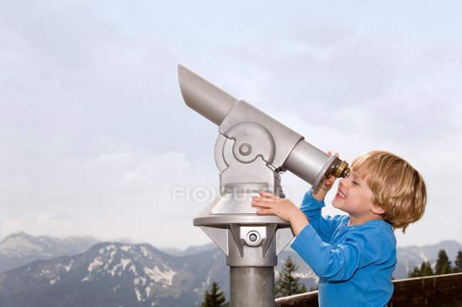 Хлопчик дивлячись через телескоп на відкритому повітрі — стокове фото