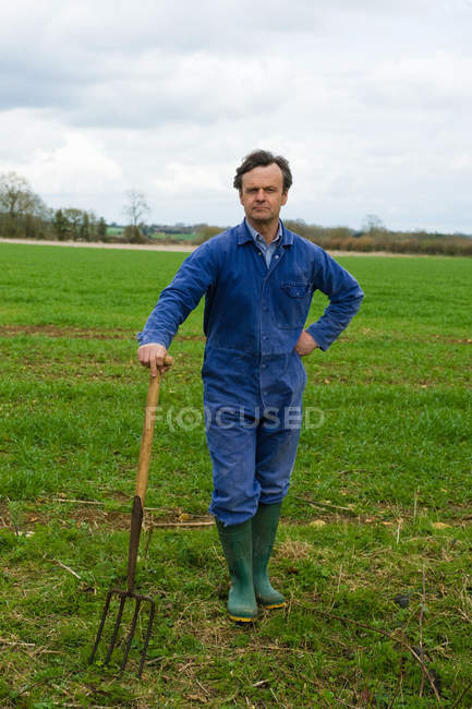 Portrait of farmer leaning on pitch fork in field — Stock Photo