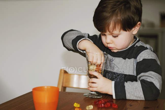 Boy playing with candy at table — Stock Photo