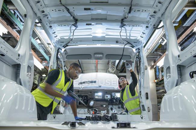 Operai che indossano giacche ad alta visibilità parti di montaggio sul veicolo sulla linea di produzione in fabbrica di auto — Foto stock