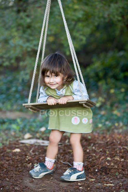 Petite fille jouant sur balançoire bois — Photo de stock