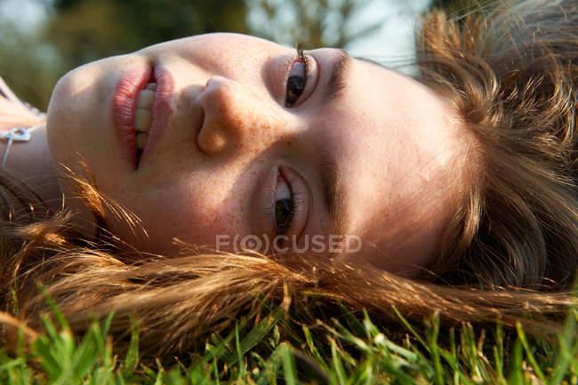 Gros plan de la fille couchée dans l'herbe — Photo de stock