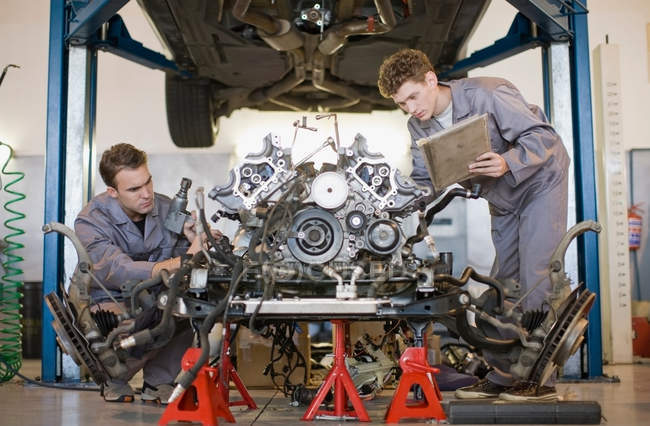 Mechanics working on car engine — Stock Photo
