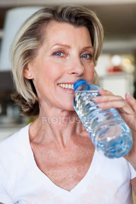 Старшая женщина пьет воду — стоковое фото