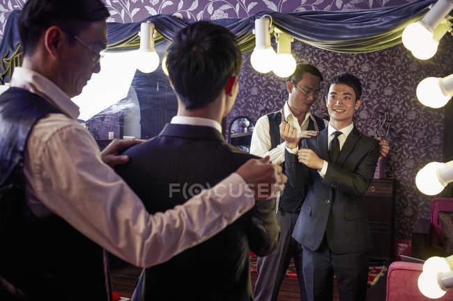 Adaptar-se com a jovem cliente masculino a experimentar um terno novo na loja tradicional — Fotografia de Stock