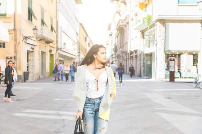 Donna in piedi in strada guardando lateralmente — Foto stock