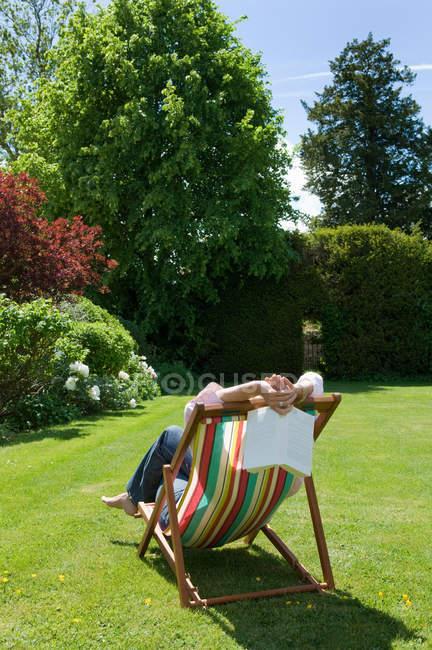 Заднього виду жінці, відпочиваючи на шезлонгу — стокове фото