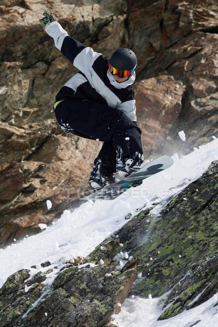 Snowboarder pulando na encosta rochosa — Fotografia de Stock
