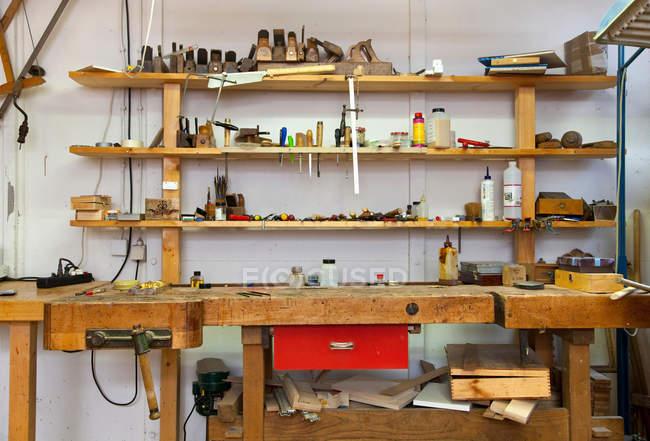 Полки и письменный стол в столярном магазине — стоковое фото