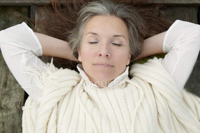 Пожилая женщина лежит на деревянном причале — стоковое фото