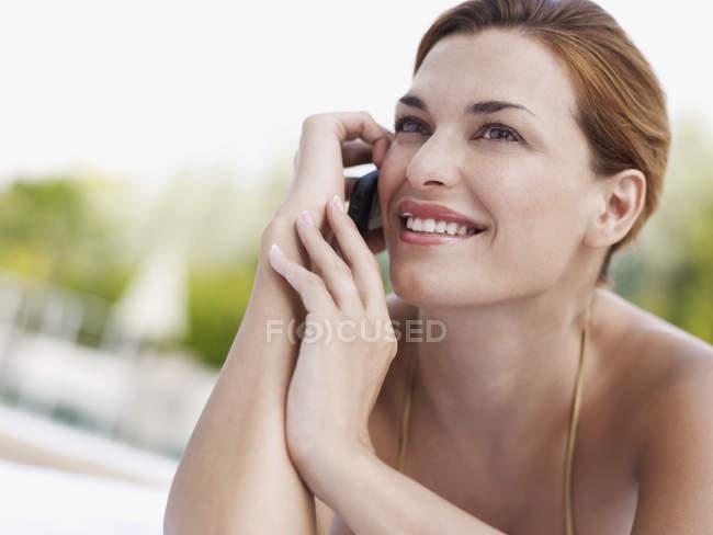 Mujer joven usando el teléfono móvil mientras toma el sol - foto de stock