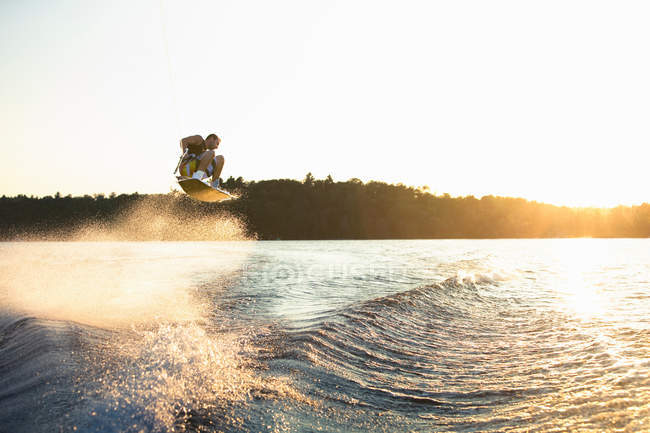 Wakeboarder jumping in the air at sunset — Stock Photo