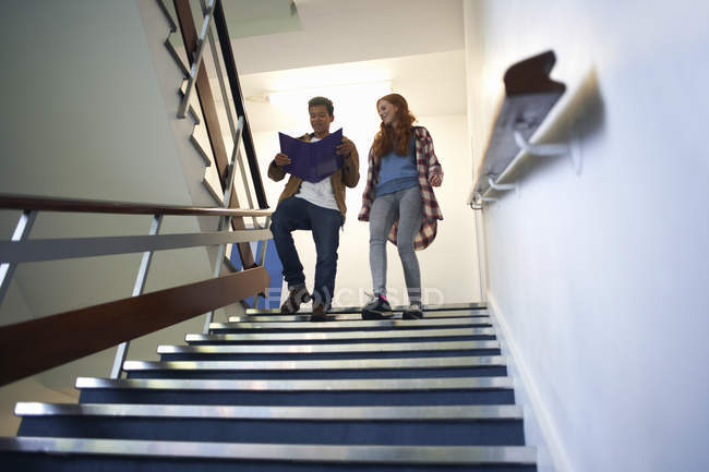 Young male and female college students moving down stairway reading file — Stock Photo