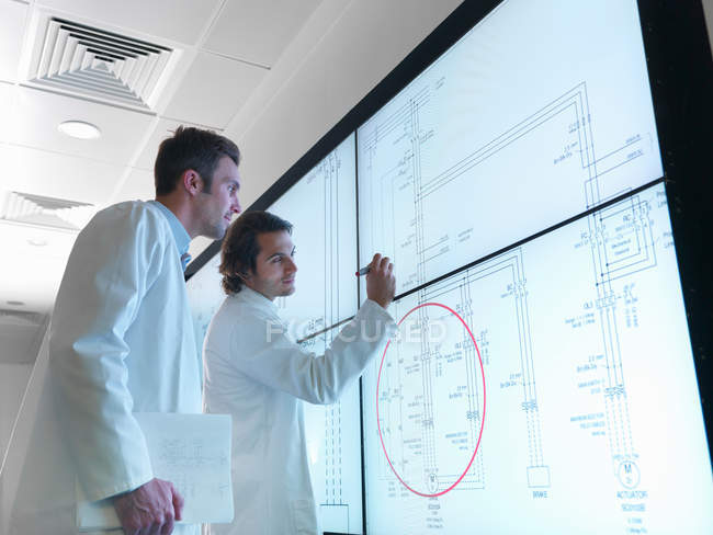 Scientists with diagrams on screen — Stock Photo