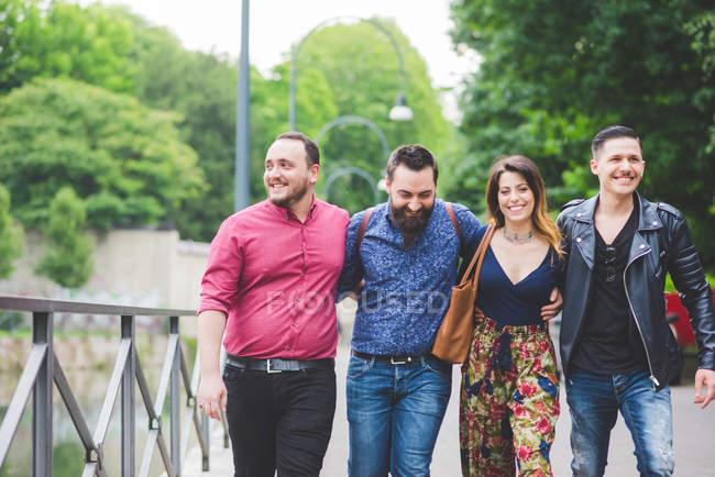Groupe d'amis marchant dans le stationnement ensemble — Photo de stock