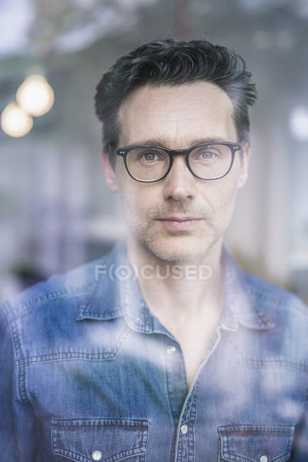 Mature businessman wearing spectacles  looking through office window — Stock Photo