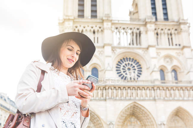 Стильний молода жінка читання смартфон в Нотр-Дам, Париж, Франція — стокове фото