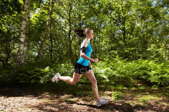 Жінка біжить лісом. — стокове фото