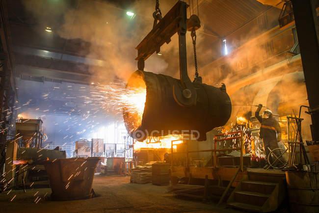 Сталевар очищает большой ковш в промышленном литейном цехе — стоковое фото
