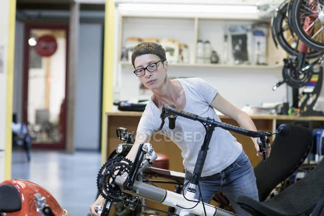 Жінка в майстерню з ремонту велосипедів перевірка педалі на лежачому велосипеді — стокове фото