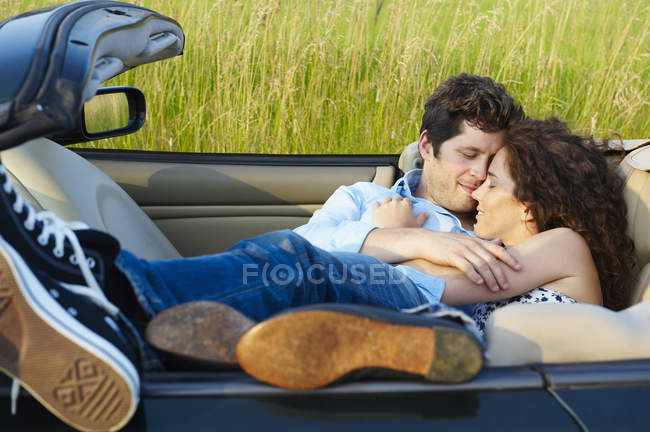 Couple laying in a convertible — Stock Photo