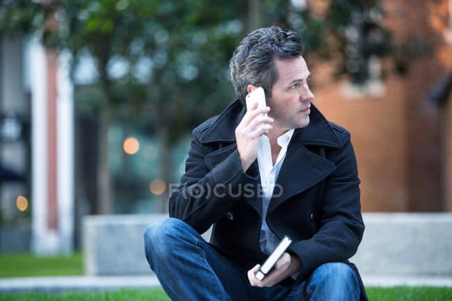 Человек, совершающий телефонный звонок с помощью смартфона, сидя на улице — стоковое фото